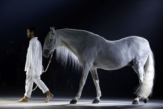 French fashion designer Simon Porte for Jacquemus walks with a horse during his 2016 Spring/Summer ready-to-wear collection fashion show, on September 29, 2015 in Paris. AFP PHOTO / FRANCOIS GUILLOT (Photo credit should read FRANCOIS GUILLOT/AFP/Getty Images)