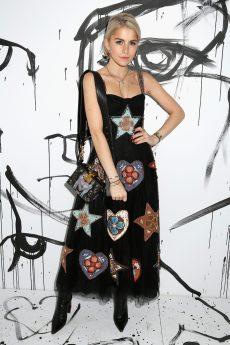 Caroline Daur portait une robe bustier en tulle noir brodé d'étoiles et de cœurs en tissus colorés Dior. Elle portait également un sac Dior.