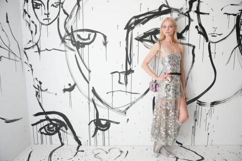 Sasha Pivovarova portait un combishort en tulle rebrodé de miroirs Dior avec une jupe du soir en tulle rebrodé de miroirs Dior. Elle portait également des bottines Dior « Naughtily D » et un sac Dior « Addict ».