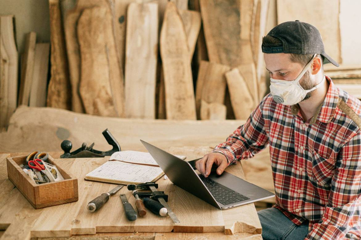 man using a laptop at a wood workshop