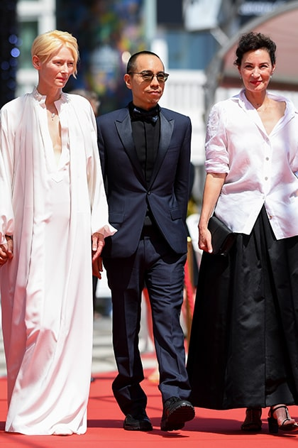 APICHATPONG WEERASETHAKUL IS DRESSED BY DIOR HE WORE A MIDNIGHT BLUE WOOL PEAK LAPEL TUXEDO, BLACK COTTON WING-TIP COLLAR SHIRT WITH PLASTRON PIQUÉ, NAVY SILK BOW-TIE WITH 'DIOR AND KENNY SCHARF' PRINT AND BLACK LEATHER DERBIES.