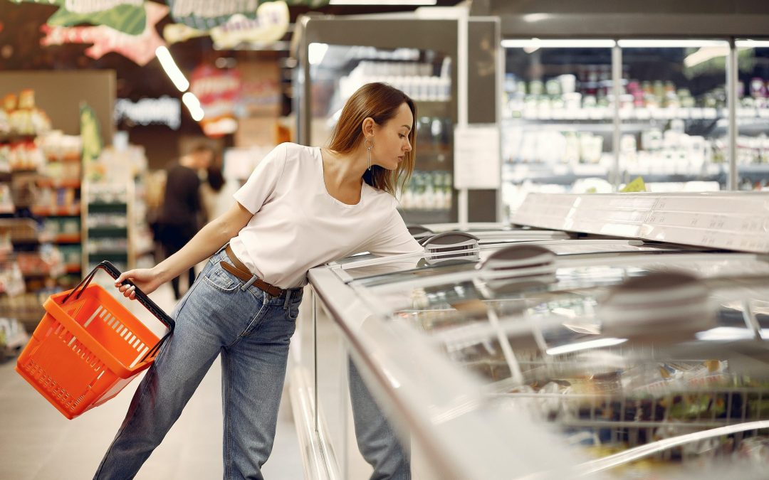 A woman picking an item from a freezer in a grocery store