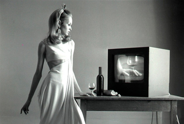 Twiggy Lawson close to a table with a bottle, a glass of wine and a piece of bread