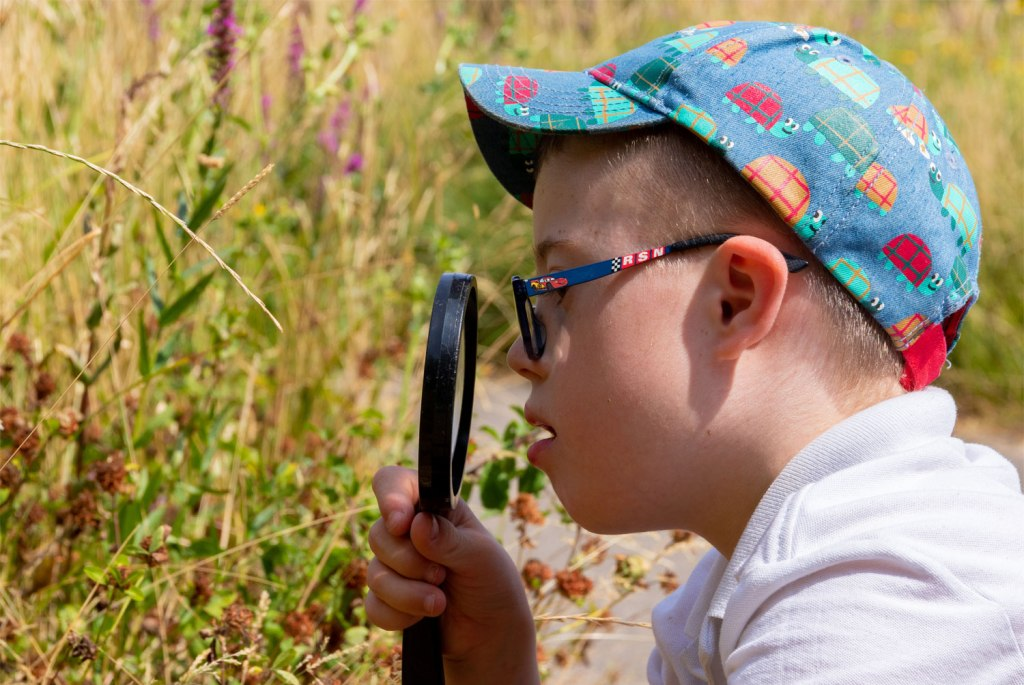Young boy studying nature with magnifying glass