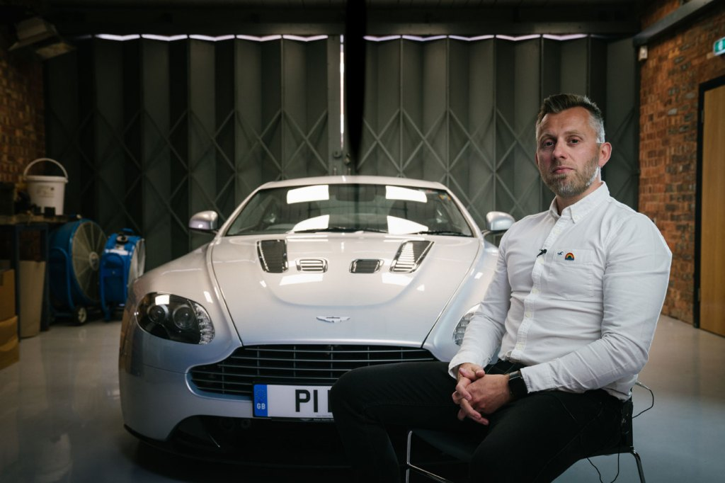 Nick Hobbis with a Vaughtons badge on an Aston Martin