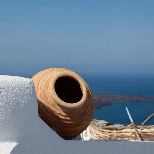 Large ceramic jar and an old row boat adorn a white washed house rooftop with the view of the caldera. Town of Fira, Santorini island, Cyclades, Greece.