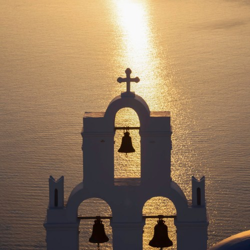 Church bells bathed in golden light of sunset. Town of Fira on the island of Santorini, Cyclades, Greece.