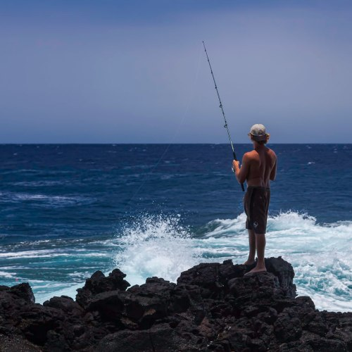 Fisherman on volcanic rocks at Kealakio Bay, Hawaii, southern most point in the United States.