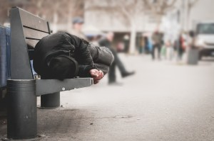 A homeless man is sleeping on bench
