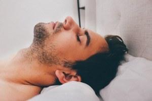 a man sleeping on a white pillow