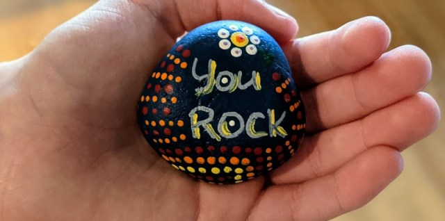 "A hand holding a rock with the words ""You Rock"""