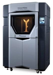 Modelo de impressora 3D da Stratsys com detalhes nas cores prata e preto. Modelo sendo impresso em 3D.