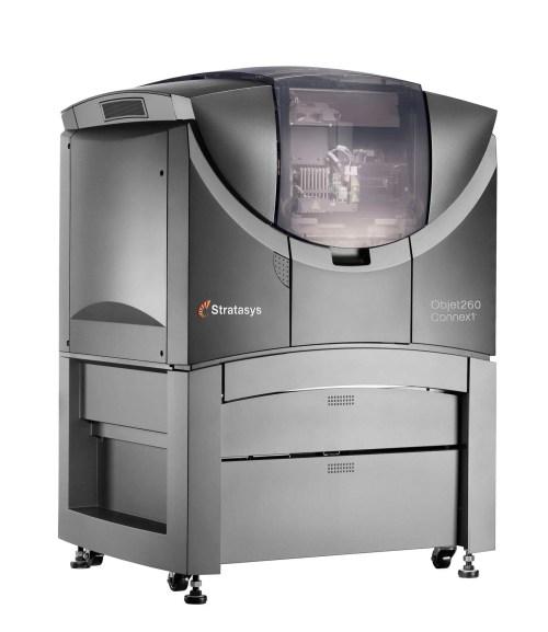 Modelo de Impressora 3D da Stratasys em cores cinca claro ao redor e cinza escuro na parte da frente. Interior de onde os protótipos são impressos posicionado a frente do modelo para melhor visualização.