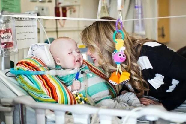 Implante respiratório criado em impressora 3D cura bebe. Mãe de bebe sorrindo para ele em quarto de hospital. Bebê sorrindo para mãe com roupinha listrada de branco e verde água.
