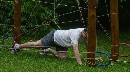 Pessoa participando de exercício em campo. Cenário gramado com um pedaço de madeira com cordas marcando obstáculos para candidato passar.
