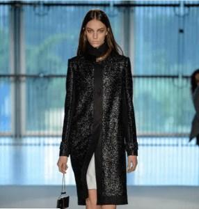 Modelo desfilando com acessório da coleção de Pedro Lourenço. Modelo usando sobre tudo preto, com clutch preta e saia branca.