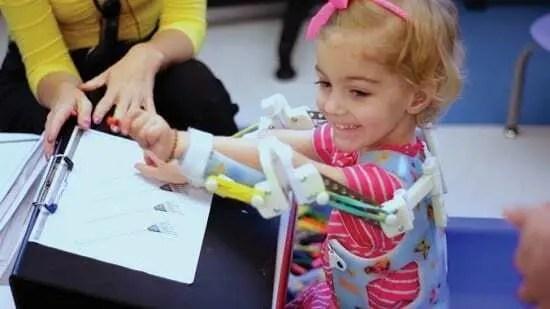 Emma usando exoesqueleto impresso em 3D. Criança com giz de cera na mão, pintando desenho em cima de uma mesa. Emma está usando blusinha rosa com listras brancas. Exoesqueleto customizado com desenhos em todo o redor.