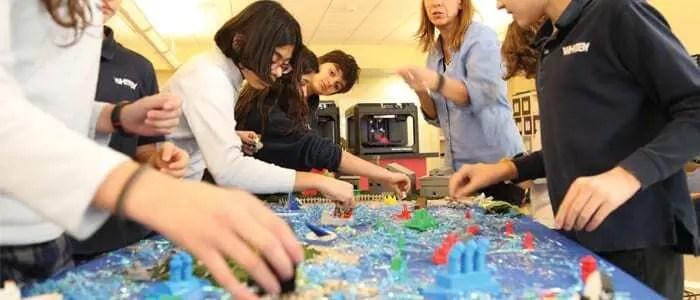 Alunos de escola americana interagindo, junto ao professor, com protótipos criados por impressora 3D em escola. Continue lendo o post!
