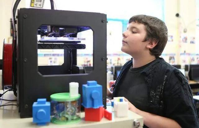 Menino olhando impressora 3D Makerbot funcionando dentro de uma escola. Continue lendo nosso post.