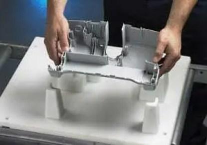 Mãos segurando peça impressa em impressora 3D. Peça na cor cinza. Confira o resto do artigo abaixo!