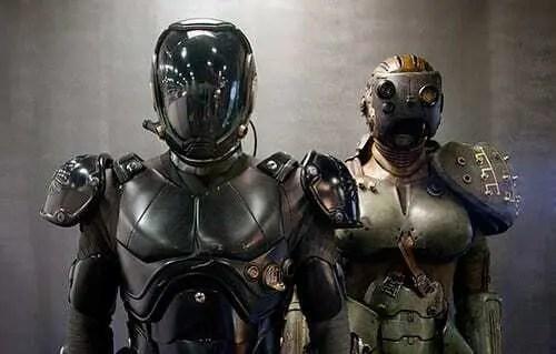 Cena no filme Coração de Fogo onde dois atores estão dentro de um ambiente utilizando armaduras com detalhes e peças impressas em 3D. Funco de cor cinza com armaduras preta e bege.