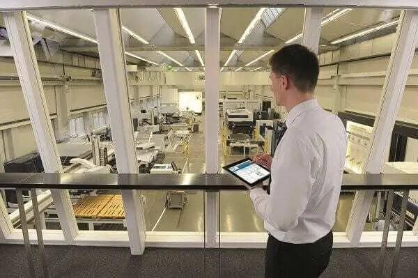 Funcionário de grande empresa vestido com roupa social (camisa branca e calça preta) segurando um tablet e coordenando as máquinas de produção que se encontram no andar de baixo de onde ele está.