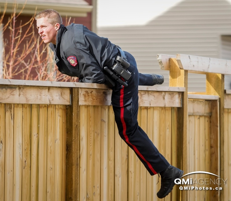 Const. Kyle McCaffrey of the Calgary Police Service climbs a fence while searching for evidence in the Chaparral Valley area of Calgary, Alta., on Wednesday October 16, 2013. A woman is dead and another suffering in hospital after an apparent stabbing in the area early in the morning. Lyle Aspinall/Calgary Sun/QMI Agency