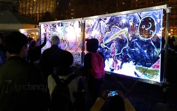 Festivalgoers draw on an illuminated board
