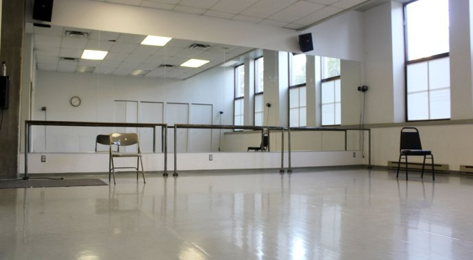 The dance studio at MAI. A room with a mirrored wall and warm-up bars, covered dance floor, large windows on on wall
