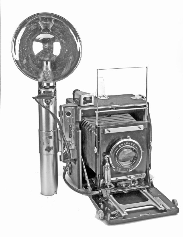 [Fig.11] Speed Graphic camera with the early Graflex Flash Synchronizer, consistingof a battery case, reflector, solenoid release attached to the lensboard, and connection cord (for use with shutters without built-in synchronization). For this to work the solenoid needs very accurate positioning.