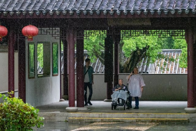 Sheltering from torrential rain (clearly visible) on a gloomy day in the Kowloon Walled City Park, ISO 4000, 1/200s at f/5, 200mm