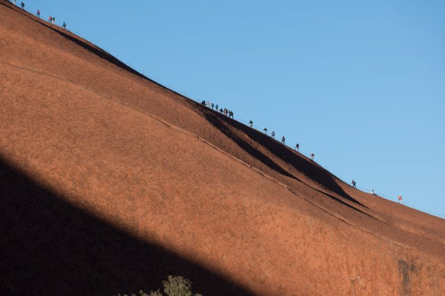 Tourists making their way up Uluru in the early morning, in spite of the requests from the indigenous owners that they respect their culture and not climb the rock. Leica CL and 55-135mm lens.