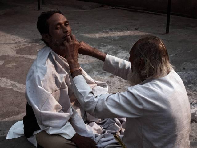 A barber gives a customer a cut in the courtyard of Khawaja Bakhtiyar Kaki's Dargah in Mehrauli.