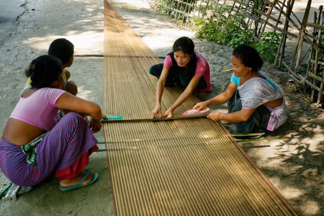Women working on a loom by the road side