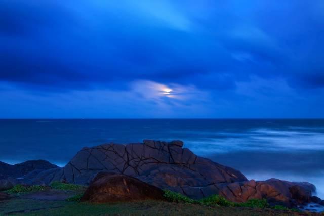 The moon over a calm sea at dawn