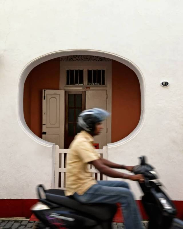 A scooterist is framed by a house's distinctive porch as he zips by on Church Street