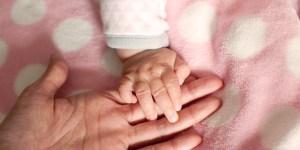 赤ちゃんがママの手を掴んでいる写真