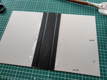 Next, glue a strip of cover material to both sides of the cardboard.