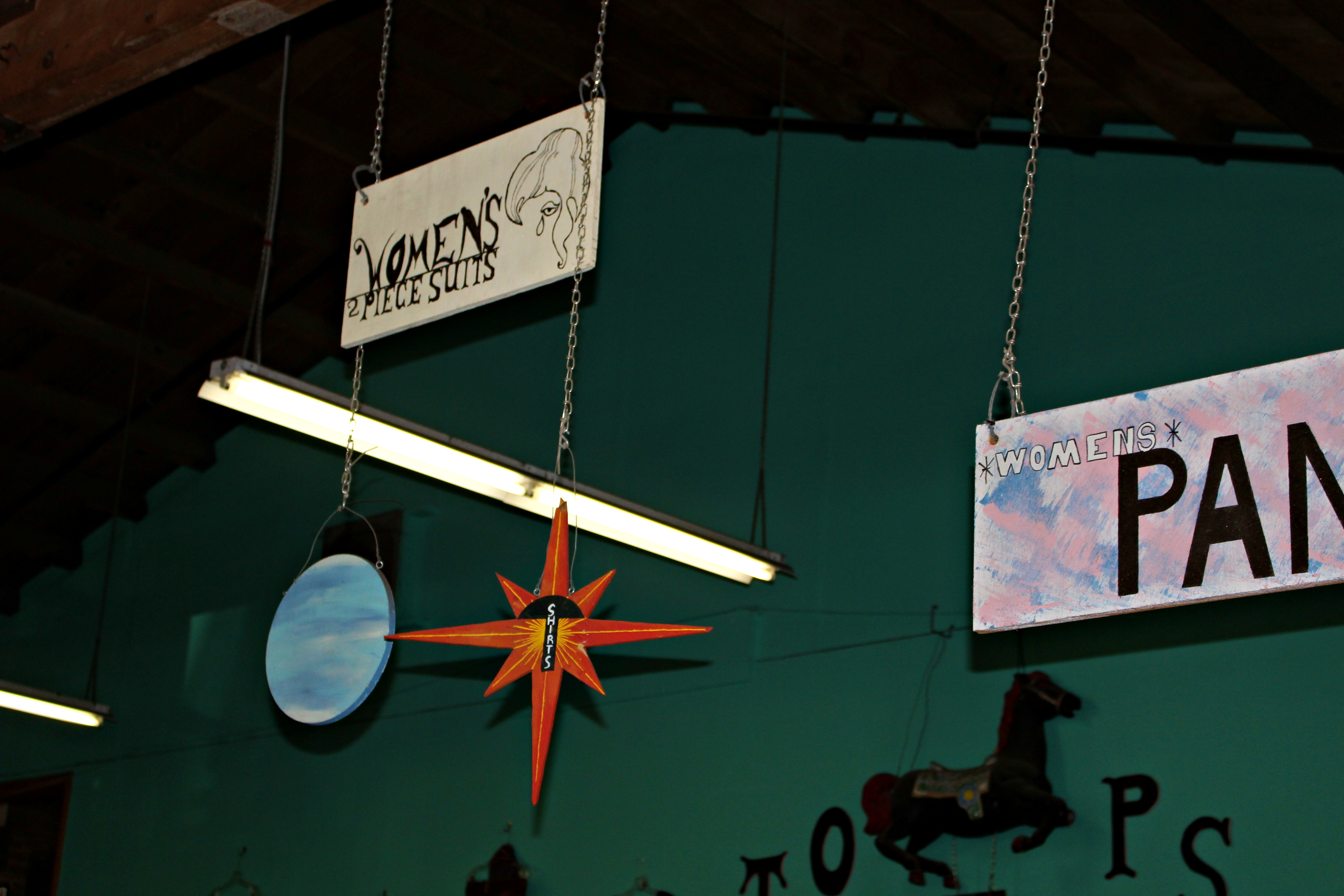 Clothing sections signs hang from the ceiling. Credit: Fiona Belk / M-A Chronicle.