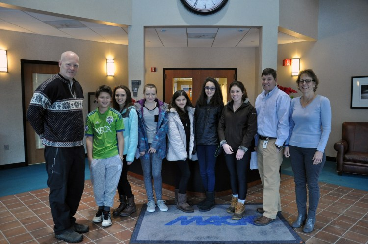 Pictured, from left, are Long Trail School Director of College Consulting & Athletics Scott Magrath with students Bryce Coe, sixth grade; Savannah Petrossi, seventh grade; Ella Masker, seventh grade; Sophia Berumen, sixth grade; Shaye Squillante, eighth grade and Shayla Sisters, eighth grade; along with Mack Molding HQ Plant Manager Rich Hornby and Director of Human Resources Nancy Cefalo. Students toured the Company's headquarters in Arlington, Vt., Wednesday, Jan. 13, 2016, to learn how business operate in the region as part of the school's Made in Vermont program.