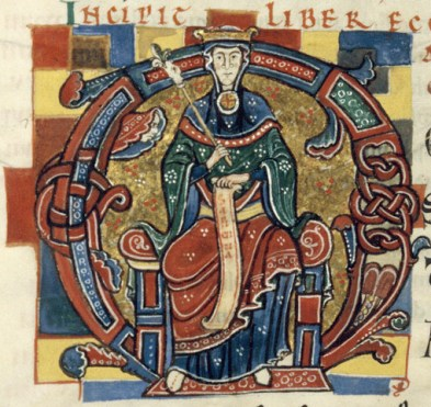 Queen wearing a cote with a overdress that is either two colored or she is wearing chape. She is also wearing a loose hood. c. 1125-1150