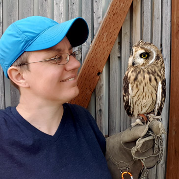 A picture of a nerd in a baseball cap holding an owl. Seriously, though.