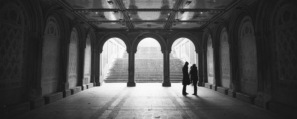 Two silhouetted figures talking in front of an architectural archway