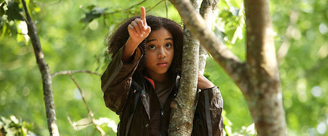 Rue from The Hunger Games film, perched in a tree and pointing upward