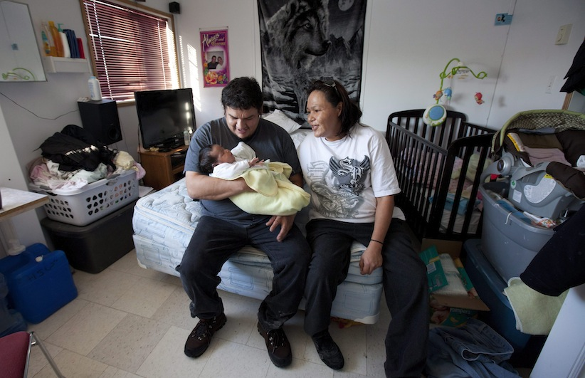 Stella Wheesk and her husband Harold Wesley hold one month old Rain Wesley in their one room home in a dorm styled temporary housing trailer in Attawapiskat, Ont., Tuesday November 29, 2011. THE CANADIAN PRESS/Adrian Wyld
