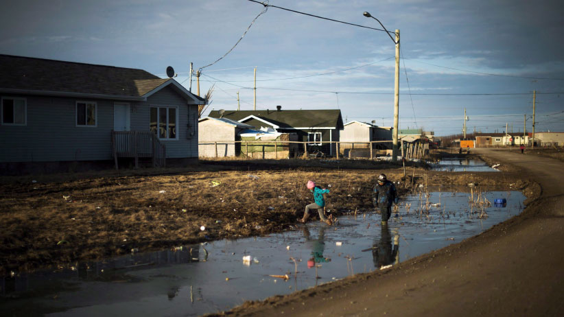 Indigenous children play in a water- filled ditch in the northern Ontario First Nations reserve in Attawapiskat, Ont., on Tuesday, April 19, 2016. In many ways, Attawapiskat - population 2,100 - has all the trappings of any small town, including older folk lamenting the changing of the times. (Nathan Denette/CP)