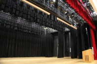 Stage features Gerriets red curtains and JD McDougall black curtains with automatic control.
