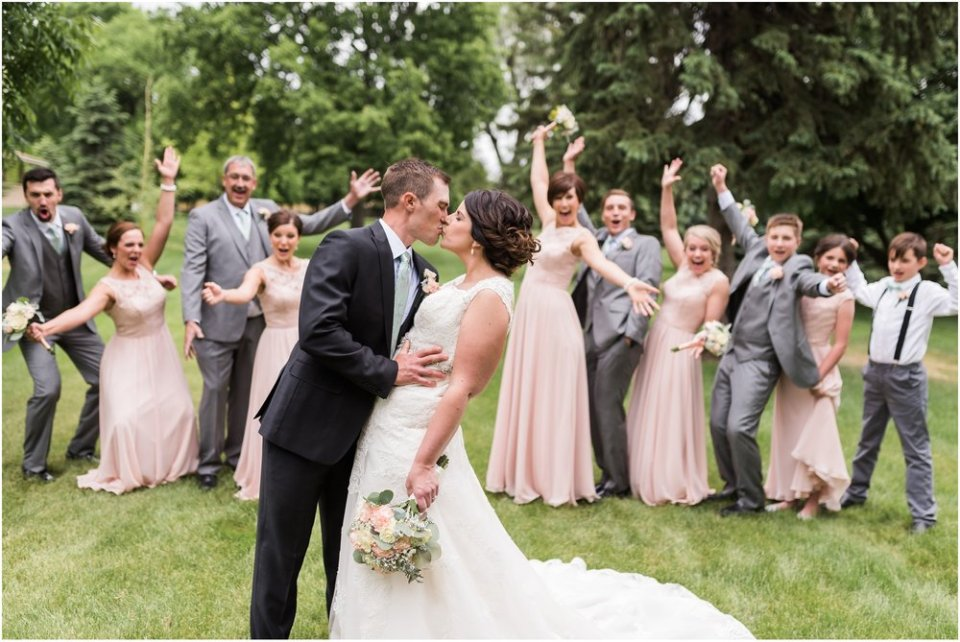 Bridal party celebrating behind bride and groom kiss | Maddie Peschong Photography