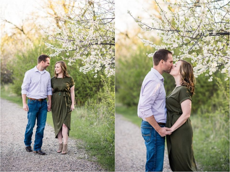 couple standing under flowering tree and kissing