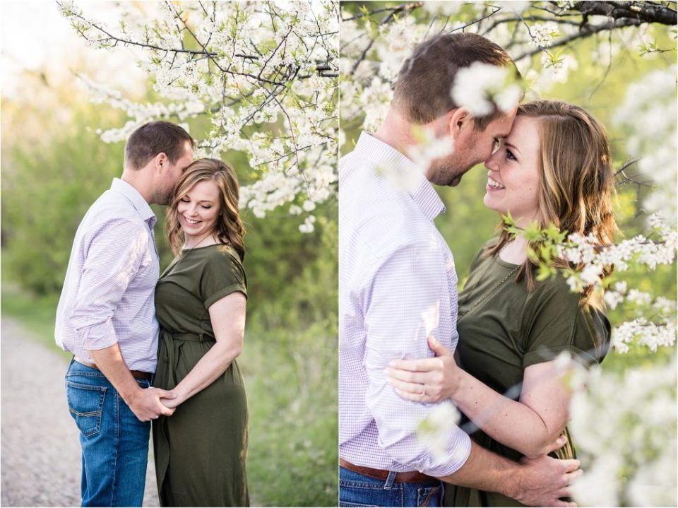 couple having sweet moment under white floral tree